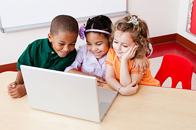 Three elementary school students working on a laptop computer.